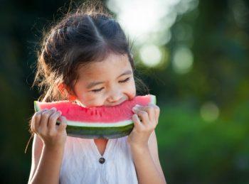 girl eats a piece of watermelon
