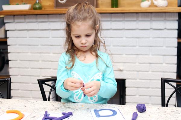 Preschooler making A with playdough