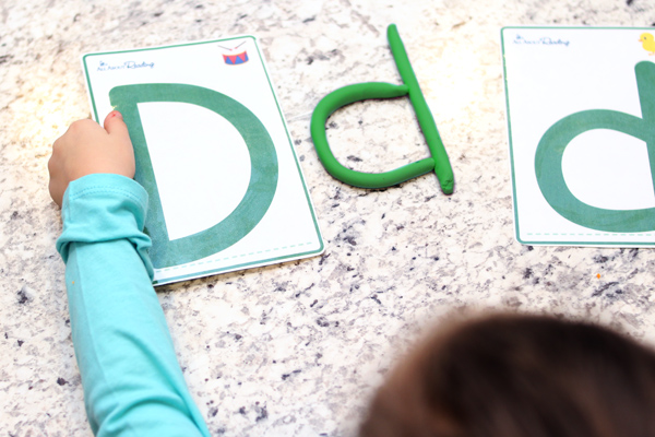 Preschooler making letters with playdough