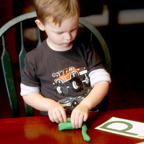 Preschooler making letter C with playdough