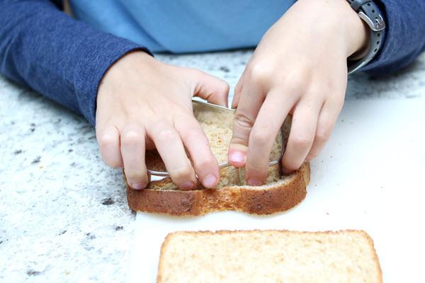 boy cuts mitten from bread