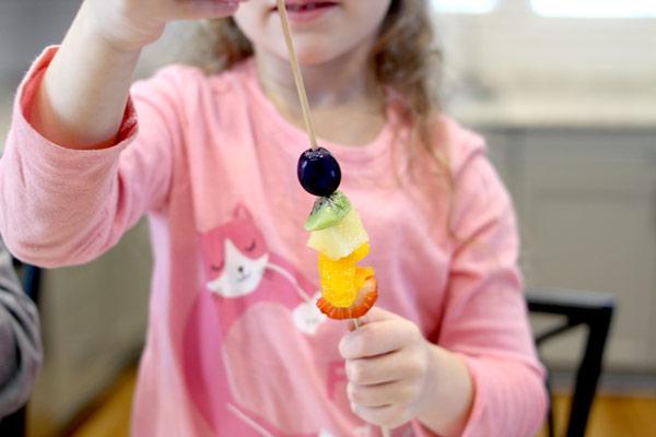 girl creating rainbow fruit skewers