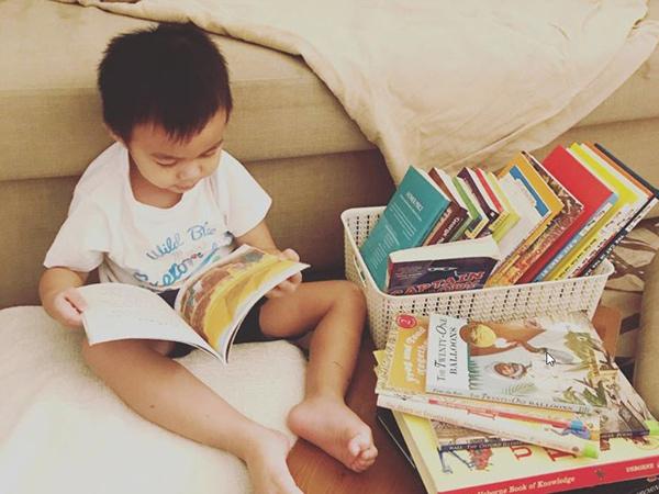 small boy reading on a soft rug
