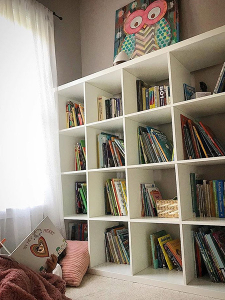 child reading book on floor by bookcase