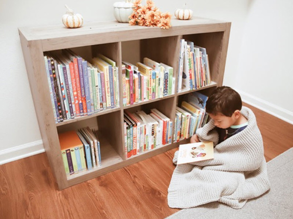 boy reading by a bookcase