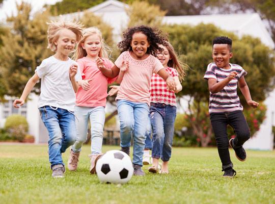 children running after a soccer ball
