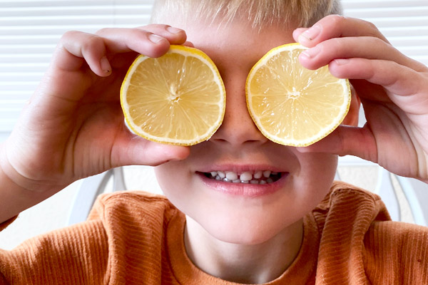 Child putting lemons to make silly face