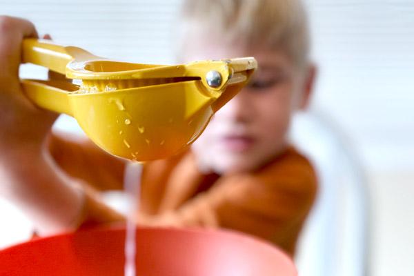Preschooler squeezing juice from a lemon