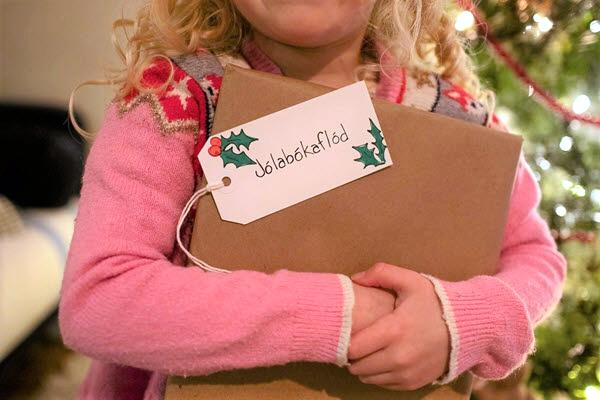 child holding a wrapped Jolabokaflod gift