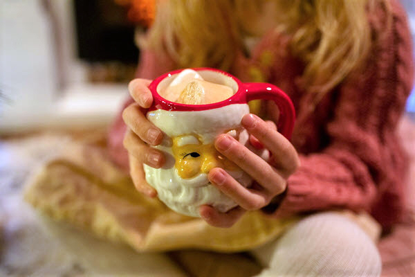 girl holding a Santa cup filled with hot chocolate