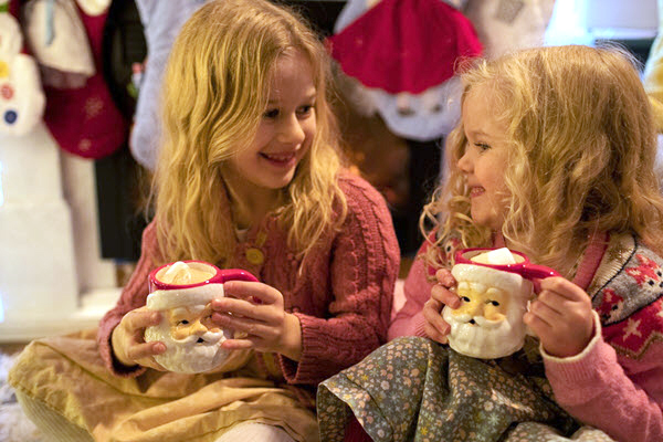 two little girls smiling and drinking hot chocolate