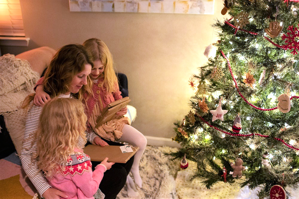 mother and two little girls opening wrapped gifts for Jolabokaflod