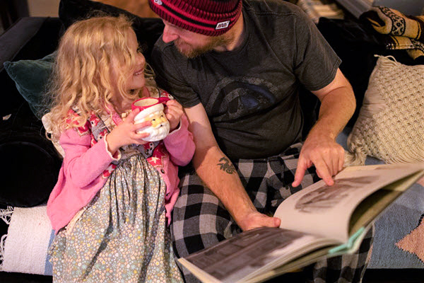 dad and child reading a picture book together for Jolabokaflod