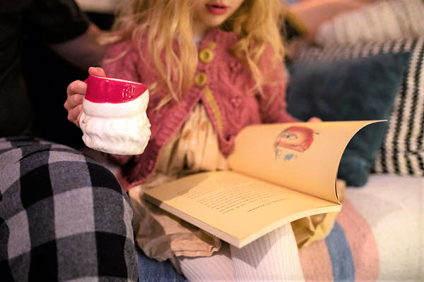 girl reading a book and drinking hot chocolate