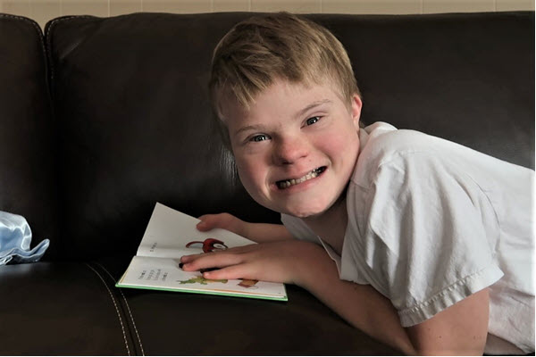 down syndrome boy reading a book with a big smile on his face