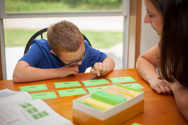 boy with down syndrome reading word cards